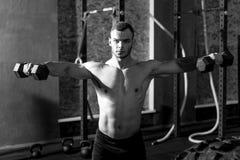 Zekere gebaarde mens die zich op het gewichtheffen concentreren Royalty-vrije Stock Foto's