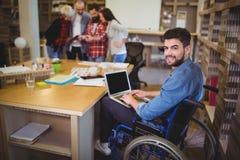 Zekere gehandicapte zakenman die laptop met behulp van bij bureau Stock Afbeeldingen