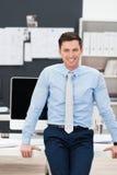 Zekere glimlachende zakenman in zijn bureau Stock Afbeeldingen