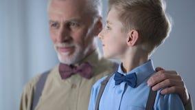 Zekere grootvader die kleinzoon, trots van jong geitje, familiesteun en zorg koesteren stock video