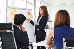 Zekere jonge Aziatische bedrijfsvrouw die strategieën op tikgrafiek verklaren aan collega's in bestuurskamer royalty-vrije stock fotografie
