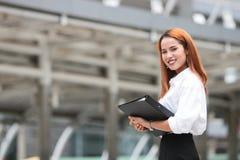 Zekere jonge Aziatische bedrijfsvrouw met ringsbindmiddel die zich op buitenkantoor bevinden Royalty-vrije Stock Afbeeldingen