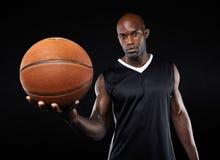 Zekere jonge basketbalspeler met een bal Royalty-vrije Stock Afbeelding
