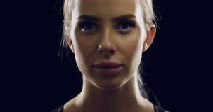 Zekere jonge blondevrouw in zwarte studio Stock Afbeelding