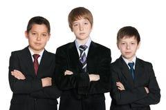 Zekere jonge jongens in zwarte kostuums Stock Afbeeldingen