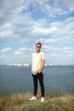 Zekere jonge mens in zonnebril op een natuurlijke achtergrond Een kerel die zich dichtbij de rivier bevinden Reizend concept De r stock foto