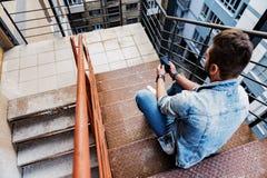 Zekere jonge mensenzitting op treden met cellphone royalty-vrije stock fotografie