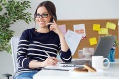 Zekere jonge vrouw die in haar bureau met mobiele telefoon werken Royalty-vrije Stock Foto's