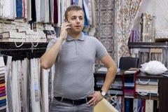 Zekere jonge zakenman, de eigenaar die van de stoffenopslag op de telefoon, achtergrondtoonzaal binnenlandse stoffen spreken stock foto