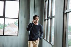Zekere jonge zakenman die celtelefoon met behulp van royalty-vrije stock foto's