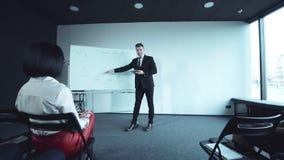 Zekere jonge zakenman die een presentatie doen stock footage