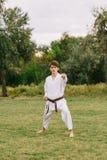 Zekere karatejongen in witte kimono op een parkachtergrond Oefent in openlucht concept uit De ruimte van het exemplaar royalty-vrije stock fotografie