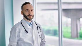 Zekere Kaukasische mannelijke arts die in witte laboratoriumlaag camera onderzoeken stock videobeelden