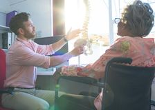 Zekere mannelijke arts die anatomisch model tonen aan hogere vrouw royalty-vrije stock foto