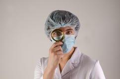 Zekere mannelijke arts die op middelbare leeftijd een vergrootglas voor zijn oog houden Royalty-vrije Stock Foto