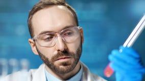 Zekere mannelijke chemicus die glazen dragen die bloedanalyse maken die beker in laboratorium met behulp van stock videobeelden