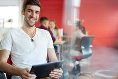 Zekere mannelijke ontwerper die aan een digitale tablet in rode creatieve bureauruimte werken Stock Afbeelding