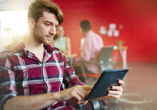 Zekere mannelijke ontwerper die aan een digitale tablet in rode creatieve bureauruimte werken Stock Afbeeldingen