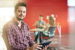 Zekere mannelijke ontwerper die aan een digitale tablet in rode creatieve bureauruimte werken Stock Foto's