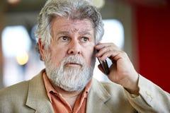 Zekere mannelijke ontwerper die op een mobiele telefoon in rode creatieve bureauruimte spreken Stock Afbeeldingen