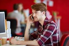 Zekere mannelijke ontwerper die op een mobiele telefoon in rode creatieve bureauruimte spreken Royalty-vrije Stock Foto