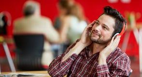 Zekere mannelijke ontwerper die op een mobiele telefoon in rode creatieve bureauruimte spreken Royalty-vrije Stock Foto's
