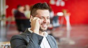 Zekere mannelijke ontwerper die op een mobiele telefoon in rode creatieve bureauruimte spreken Stock Fotografie
