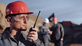 Zekere mannelijke voormanarbeider die gebruikend walkie-talkie in bouwwerf bij zonsondergang bespreken stock footage
