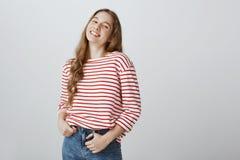 Zekere medewerker tevreden met positief resultaat Gelukkige tevreden Europese vrouwelijke holdingshanden op zakken, het glimlache royalty-vrije stock foto's