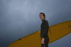 Zekere Mens die met Surfplank weg tegen Bewolkte Hemel kijken Stock Fotografie