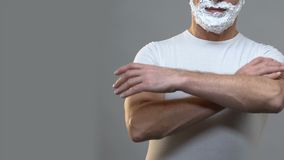 Zekere mens die zich met gekruiste handen en het scheren schuim op gezicht, hygiëne bevinden stock video