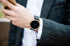 Zekere mens in grijs jasje die smartphone, elegante zaken gebruiken Stock Afbeeldingen