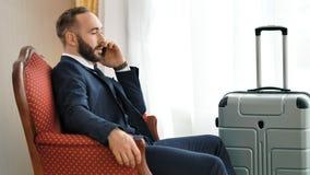 Zekere modieuze mannelijke zakenman die probleem bespreken die gebruikend smartphone bij hotelruimte spreken stock footage