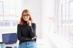 Zekere onderneemster die aan u glimlachen en camera bekijken terwijl status in het bureau stock afbeelding