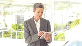 Zekere onderneemster gebruikend tablet en bekijkend camera stock video