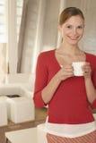 Zekere Onderneemster Holding Coffee Cup in Bureauhal royalty-vrije stock foto's