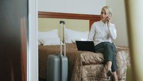 Zekere onderneemster in wit overhemd gebruikend op laptop en sprekend bij mobiele telefoon die terwijl het aanwezig zijn op bed g stock footage