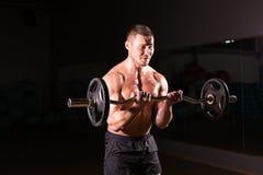 Zekere spiermens opleiding met barbell Close-upportret van professionele bodybuildertraining met barbell bij gymnastiek royalty-vrije stock afbeeldingen