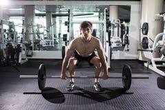 Zekere spiermens opleidingshurkzit met barbells boven Close-upportret van professionele mensentraining met barbell bij gymnastiek stock afbeeldingen