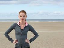 Zekere sportenvrouw die zich door het strand bevinden Stock Afbeeldingen