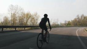 Zekere triathlete berijdende fiets Triatlon opleiding Volg schot van fietser het pedaling op fiets Langzame Motie stock videobeelden