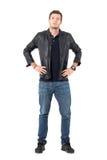 Zekere trotse toevallige mens die jasje en jeans met handen op heupen dragen die camera bekijken Royalty-vrije Stock Fotografie