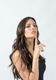 Zekere verleidelijke lange haarschoonheid met het gebaar die van de stiltevinger camera bekijken Royalty-vrije Stock Afbeeldingen