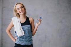 Zekere vrij jonge sportvrouw die zich met fles van water en witte handdoek bevinden royalty-vrije stock afbeelding