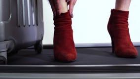 Zekere vrouw met koffer die haar modieuze rode laarzen op hoge dunne hielen verbeteren die zich op spoor bevinden Sluit omhoog stock videobeelden