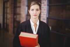 Zekere vrouwelijke advocaat met boek die zich in bureau bevinden stock foto