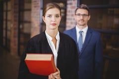 Zekere vrouwelijke advocaat met zakenman in bureau stock fotografie