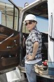 Zekere vrouwelijke fabrieksarbeider die zich door voertuigdeur bevinden met hand op heup stock afbeeldingen