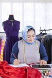 Zekere vrouwelijke moslimmanierontwerper die met kledingstukken werken royalty-vrije stock afbeeldingen