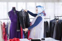 Zekere vrouwelijke moslimmanierontwerper die met kledingstukken werken stock afbeelding